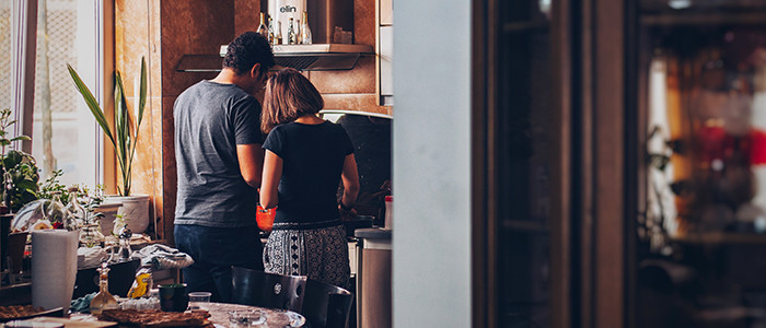 Couple cooking a meal together in a warm kitchen
